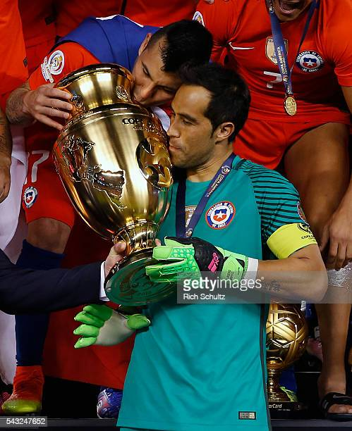 Claudio Bravo and Gary Medel of Chile kiss the trophy after winnig the championship match between Argentina and Chile at MetLife Stadium as part of...