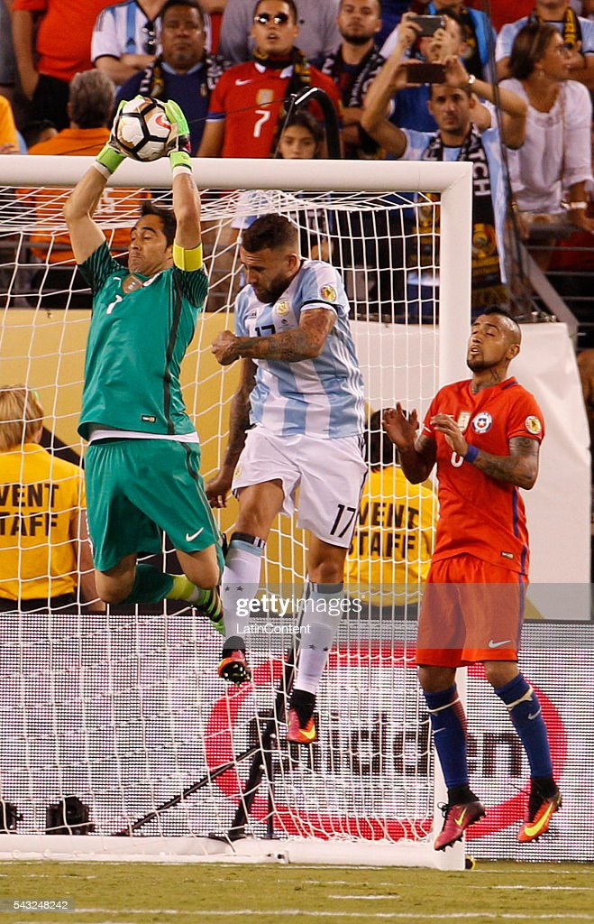 <a gi-track='captionPersonalityLinkClicked' href=/galleries/search?phrase=Claudio+Bravo&family=editorial&specificpeople=2715784 ng-click='$event.stopPropagation()'>Claudio Bravo</a> of Chile leaps to catch the ball in front of <a gi-track='captionPersonalityLinkClicked' href=/galleries/search?phrase=Nicolas+Otamendi&family=editorial&specificpeople=5863368 ng-click='$event.stopPropagation()'>Nicolas Otamendi</a> of Argentina during extra time in the championship match between Argentina and Chile at MetLife Stadium as part of Copa America Centenario US 2016 on June 26, 2016 in East Rutherford, New Jersey, US.