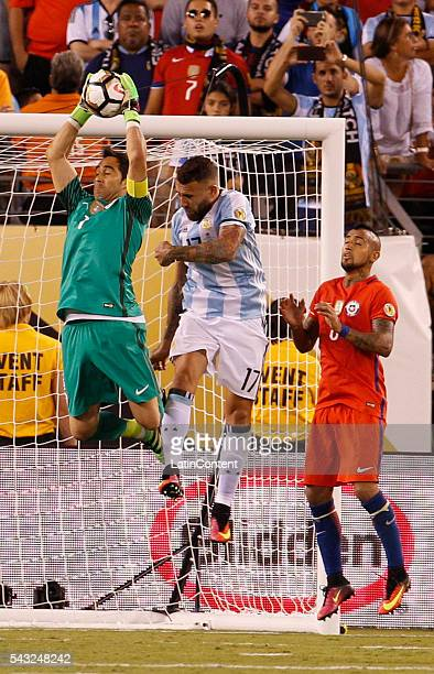 Claudio Bravo of Chile leaps to catch the ball in front of Nicolas Otamendi of Argentina during extra time in the championship match between...