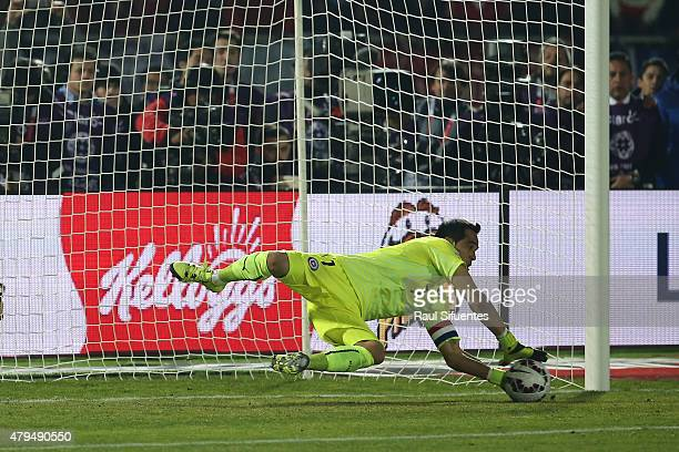 Claudio Bravo of Chile saves the third penalty shooted by Ever Banega of Argentina in the shootout during the 2015 Copa America Chile Final match...
