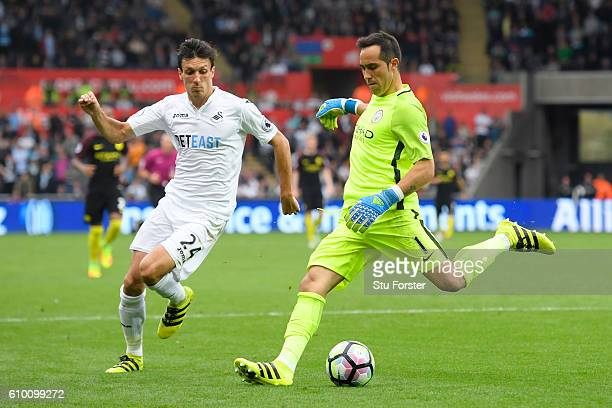 Claudio Bravo of Manchester City is put under pressure from Jack Cork of Swansea City from during the Premier League match between Swansea City and...