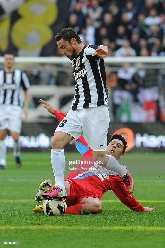 Claudio Marchisio (L) of FC Juventus is tackled by Lucas Nahuel Castro of Calcio Catania during the Serie A match between FC Juventus and Calcio Catania at Juventus Arena on March 10, 2013 in Turin, Italy.