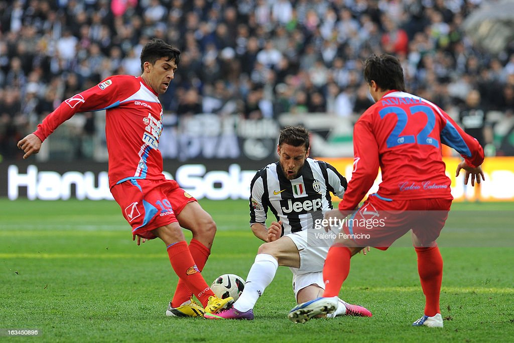 Claudio Marchisio of FC Juventus is tackled by Lucas Nahuel Castro (L) of Calcio Catania during the Serie A match between FC Juventus and Calcio Catania at Juventus Arena on March 10, 2013 in Turin, Italy.