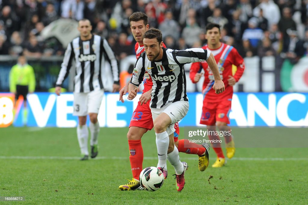 Claudio Marchisio of FC Juventus takes the ball past Mariano Julio Izco of Calcio Catania during the Serie A match between FC Juventus and Calcio Catania at Juventus Arena on March 10, 2013 in Turin, Italy.