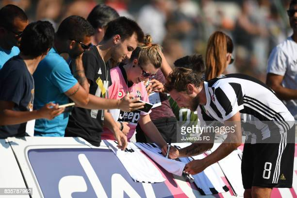 Claudio Marchisio of Juventus A signs autographs for fans during the preseason friendly match between Juventus A and Juventus B on August 17 2017 in...