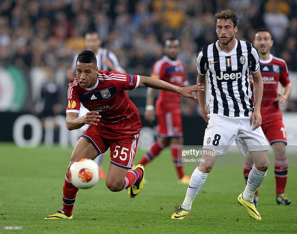 Claudio Marchisio of Juventus and Corentin Tolisso of Lyon #55 compete for the ball during the UEFA Europa League quarter final match between Juventus and Olympique Lyonnais at Juventus Arena on April 10, 2014 in Turin, Italy.