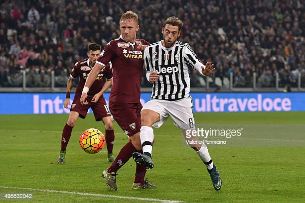 Claudio Marchisio of Juventus FC is challenged by Kamil Glik of Torino FC during the Serie A match between Juventus FC and Torino FC at Juventus...