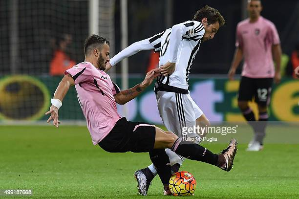 Claudio Marchisio of Juventus is challenged by Alberto Gilardino of Palermo during the Serie A match between US Citta di Palermo and Juventus FC at...