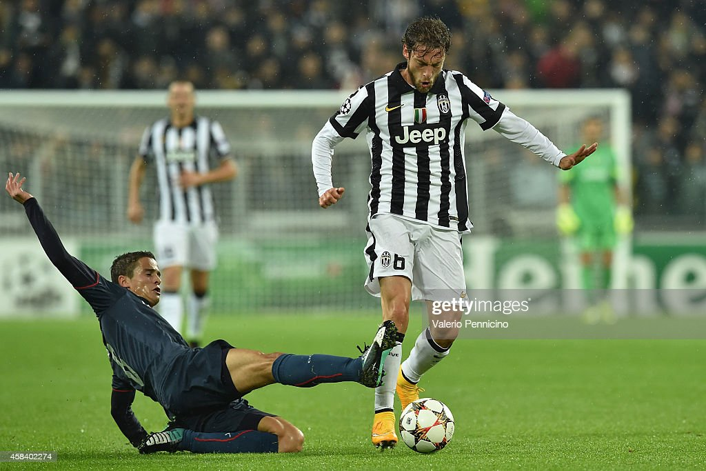 Claudio Marchisio (R) of Juventus is challenged Ibrahim Afellay of Olympiacos FC during the UEFA Champions League group A match between Juventus and Olympiacos FC at Juventus Arena on November 4, 2014 in Turin, Italy.