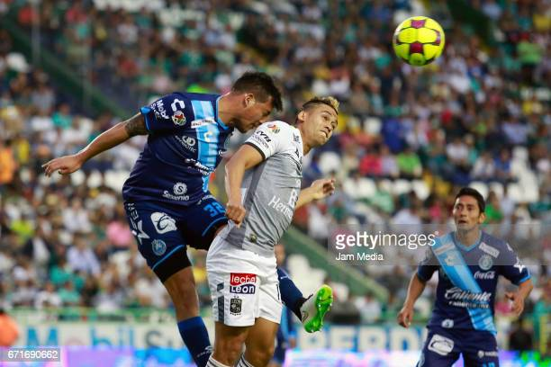 Claudio Perez of Puebla and Carlos Guzman of Leon jump to head the ball during the 15th round match between Leon and Puebla as part of the Torneo...