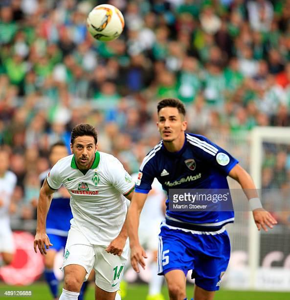 Claudio Pizarro of Bremen challenges Benjamin Huebner of Ingolstadt during the Bundesliga match between Werder Bremen and FC Ingolstadt at...