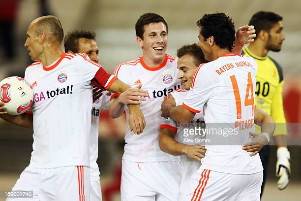 Claudio Pizarro of Muenchen celebrates his team's third goal with team mates during the international friendly match between Lekhwiya Sports Club and...