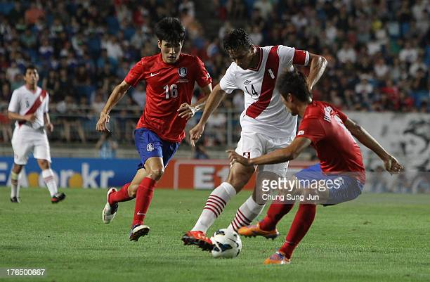 Claudio Pizarro of Peru compete for the ball with Hwang SeokHo and Han KookYoung of South Korea during the international friendly match between South...