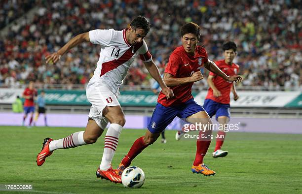 Claudio Pizarro of Peru compete for the ball with Hwang SeokHo of South Korea during the international friendly match between South Korea and Peru at...