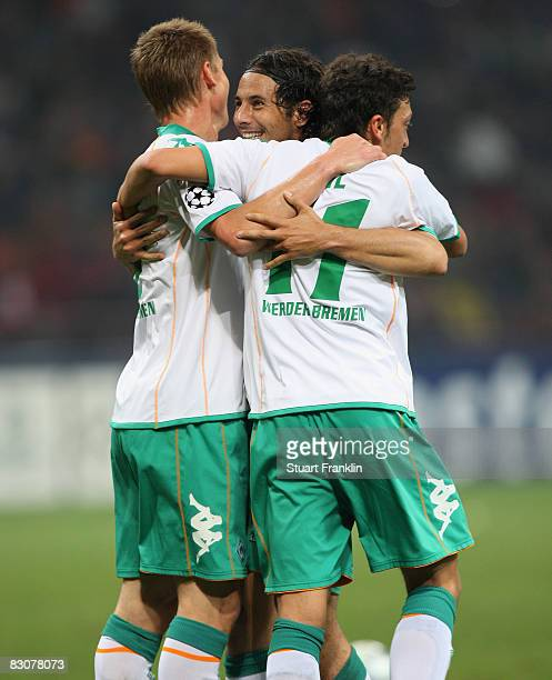 Claudio Pizzaro of Bremen celebrates his goal with Markus Rosenberg and Mesut Ozil during the UEFA Champions League Group B first leg match between...