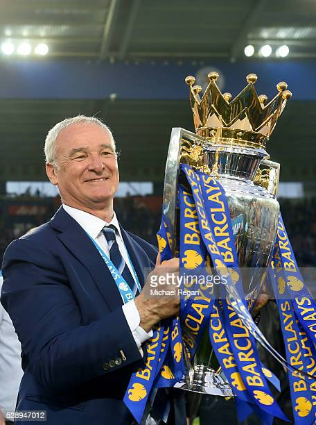 Claudio Ranieri poses for photographs with the Premier League Trophy as players and staffs celebrate the season champions after the Barclays Premier...