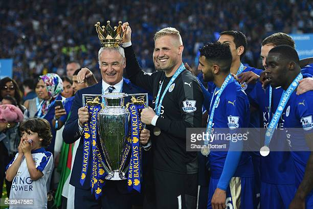 Claudio Ranieri poses with the Premier League Trophy while Kasper Schmeichel puts the crown on the head of the manager as players and staffs...