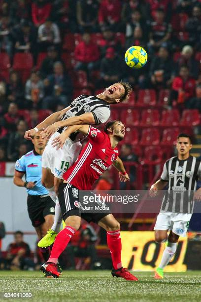 Claudio Riano of Necaxa heads the ball over the mark of Guido Rodriguez ofTijuana during the 6th round match between Tijuana and Necaxa as part of...