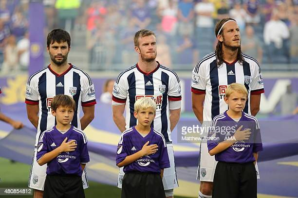 Claudio Yacob Chris Brunt and Chris Brunt of West Bromwich Albion as the mascots sing the national anthem during the preseason friendly between...