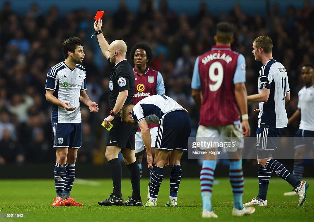 Claudio Yacob of West Bromwich Albion (L) is shown a red card by referee Anthony Taylor and is sent off during the FA Cup Quarter Final match between Aston Villa and West Bromwich Albion at Villa Park on March 7, 2015 in Birmingham, England.