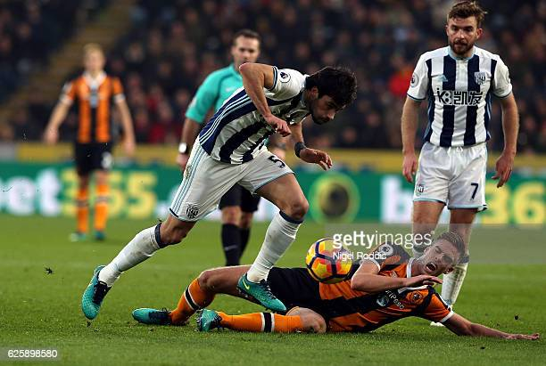 Claudio Yacob of West Bromwich Albion is tackled by Markus Henriksen of Hull City during the Premier League match between Hull City and West Bromwich...