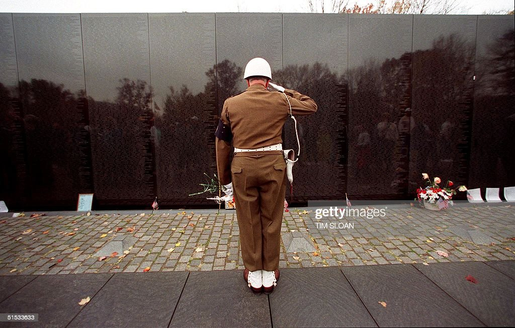Claudius M. Lehmann, a US Army World War II and Korean War veteran from Ashburn, VA salutes after placing a red carnation at the Vietnam Memorial Wall 11 November, 1999 in Washington, DC. Lehmann placed flowers along the wall in observance of Veteran's Day.