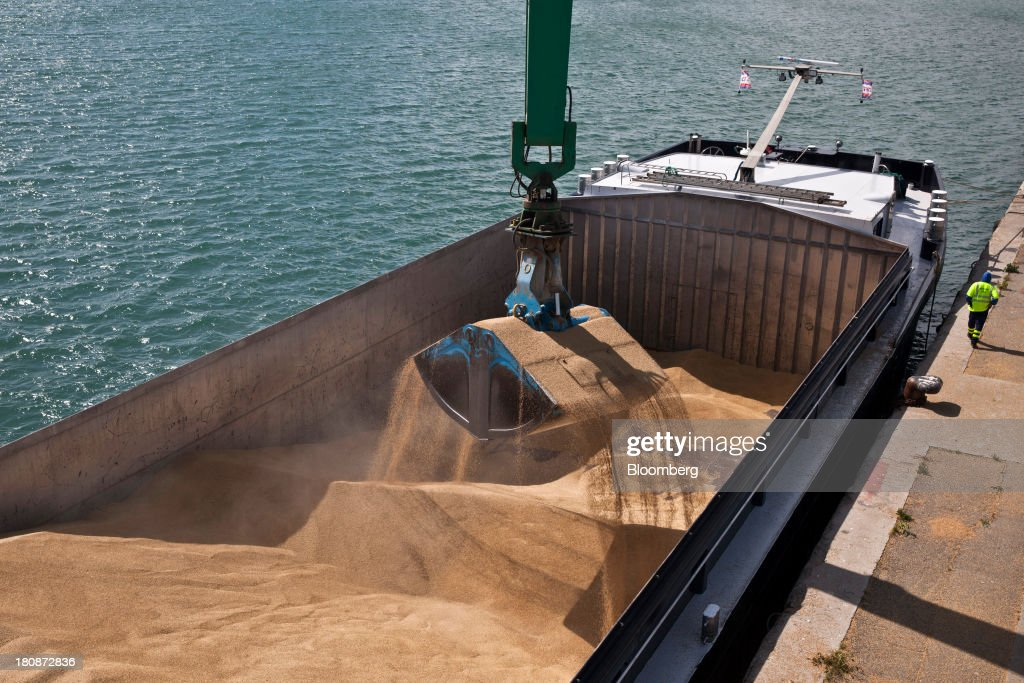 A claw crane grabs a bucket of winter barley from the hold of the cargo barge 'Poseidon' during operations at Tellines Port, operated by the Marseille-Fos Port Authority in Port Saint Louis du Rhone, France, on Monday, Sept. 16, 2013. European Union average corn yields will be lower than expected last month after hot and dry weather in Italy during flowering in August hurt the grain, according to the bloc's crop-monitoring unit. Photographer: Balint Porneczi/Bloomberg via Getty Images