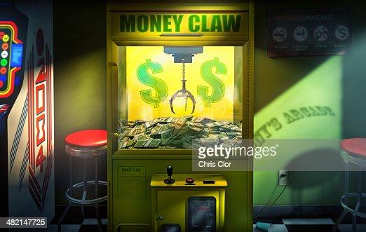 Claw grabbing money in money claw arcade machine