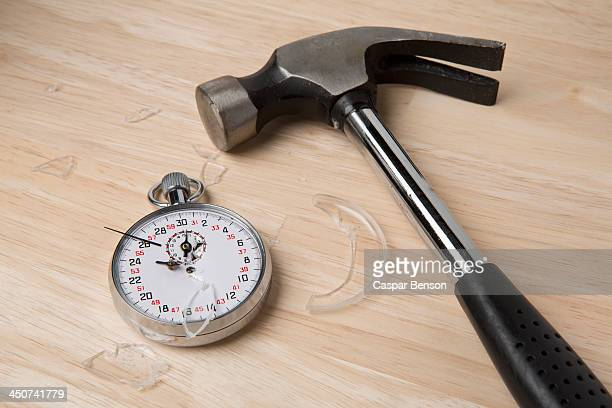A claw hammer lying next to a broken stopwatch