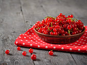 Freshly picked redcurrant berries in a clay bowl on a rustic table. The concept of healthy natural food.