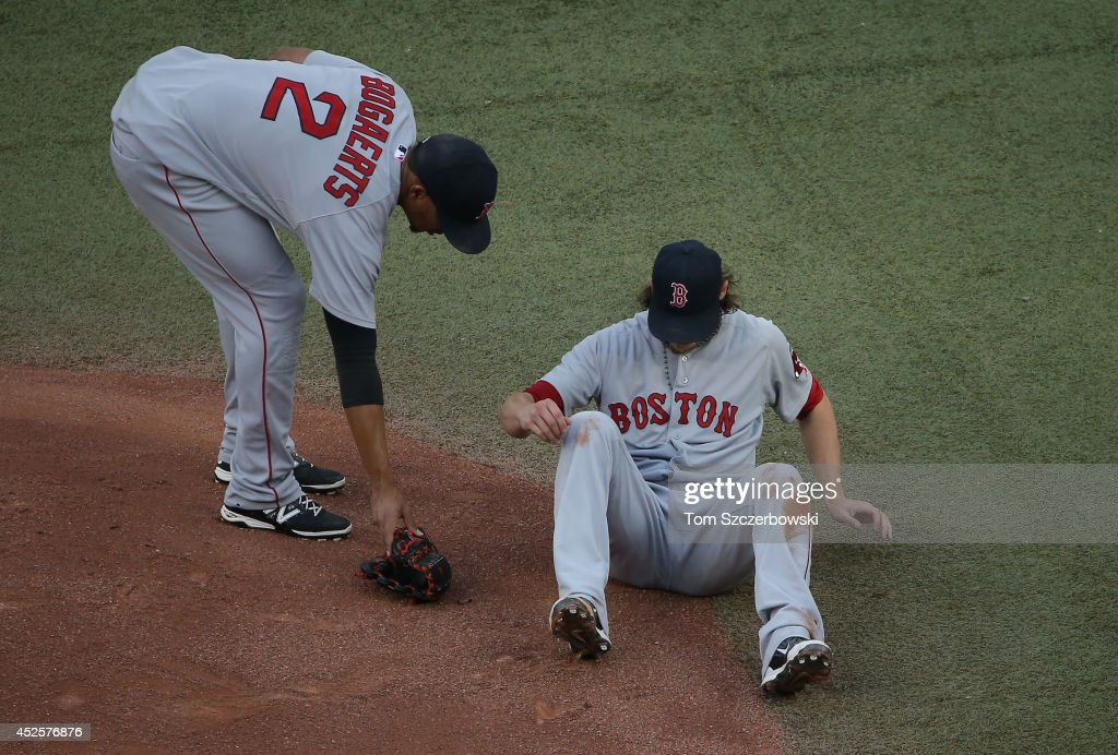 Clay Buchholz #11 of the Boston Red Sox falls after being hit by a line drive as Xander Bogaerts #2 helps him pick up his glove in the first inning during MLB game action against the Toronto Blue Jays on July 23, 2014 at Rogers Centre in Toronto, Ontario, Canada.