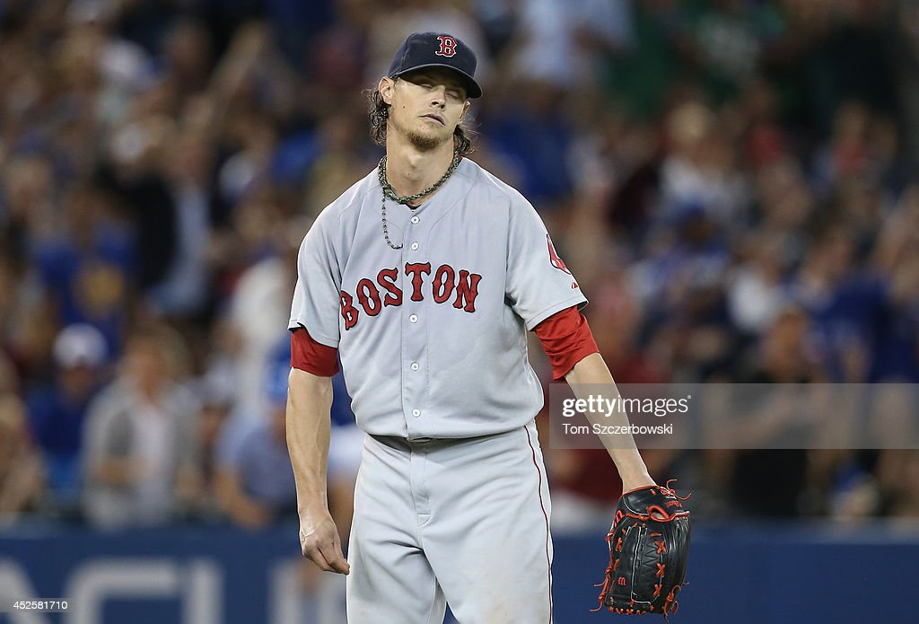 <a gi-track='captionPersonalityLinkClicked' href=/galleries/search?phrase=Clay+Buchholz&family=editorial&specificpeople=4424901 ng-click='$event.stopPropagation()'>Clay Buchholz</a> #11 of the Boston Red Sox reacts after a throwing error with two outs by <a gi-track='captionPersonalityLinkClicked' href=/galleries/search?phrase=Xander+Bogaerts&family=editorial&specificpeople=9461957 ng-click='$event.stopPropagation()'>Xander Bogaerts</a> #2 led to an unearned run in the sixth inning during MLB game action against the Toronto Blue Jays on July 23, 2014 at Rogers Centre in Toronto, Ontario, Canada.