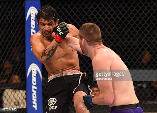 Clay Collard of the United States punches Gabriel Benitez of Mexico in their featherweight bout during the UFC 188 event at the Arena Ciudad de...