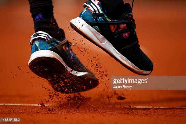 Clay falls from the shoes of Gilles Simon of France as he serves during his Men's Singles match against Nicolas Mahut of France on day six of the...
