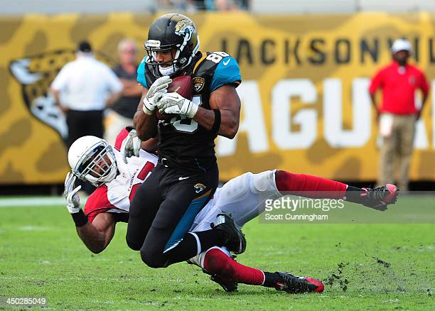 Clay Harbor of the Jacksonville Jaguars makes a catch against Yeremiah Bell of the Arizona Cardinals at EverBank Field on November 17 2013 in...