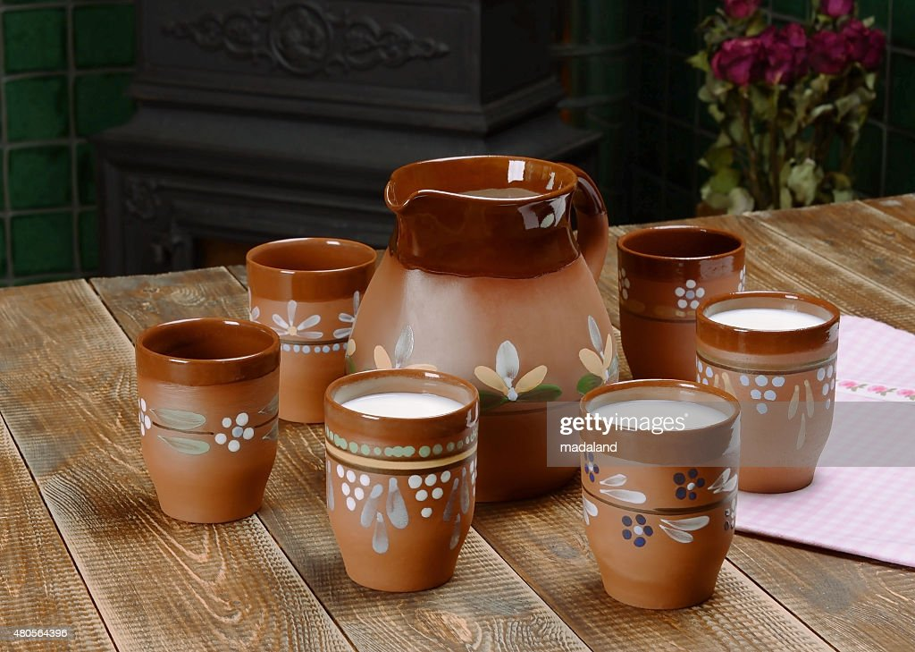 Clay jug and three cups of milk. : Stock Photo