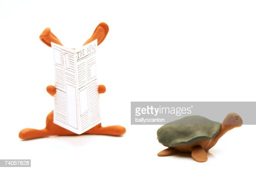 Clay model hare reading newspaper and tortoise on white background : Stock Photo