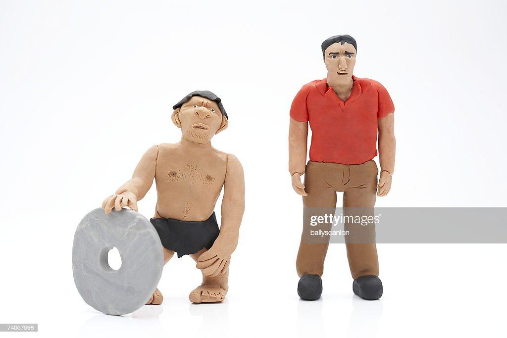 Caveman Modern Man : Clay model of caveman with stone wheel next to modern man