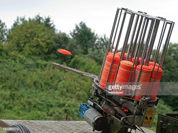 A clay pigeon is ejected out of a clay target machine