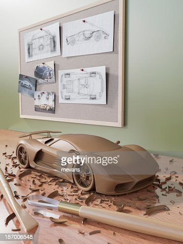 A clay sculpture of an automobile on a wooden surface