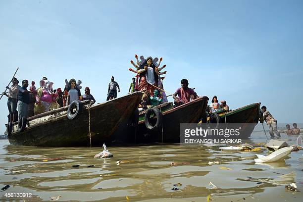 A clay statue of the Hindu goddess Durga and other deities are transported on boats from the artisan's villag of Kumartoli to a place of worship...