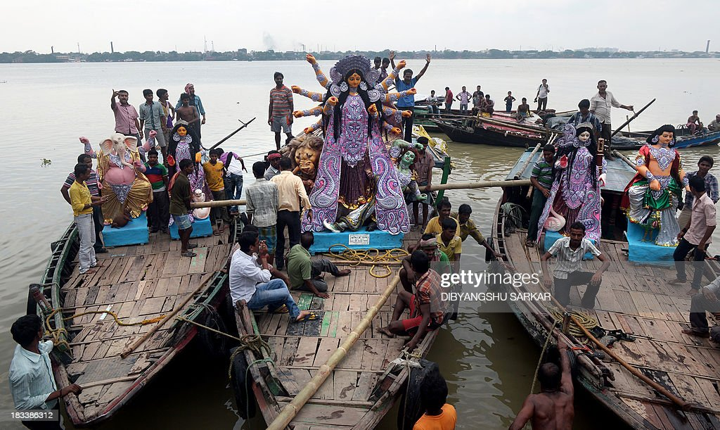 A clay statue of the Indian Hindu goddess Durga is transported from a workshop in Kumartoli, the idol makers' village, by boat on the river Ganges to a place of worship in Kolkata on October 6, 2013. Late monsoon rain and rising inflation add to the difficulties of the artisans in their business ahead of the five-day Durga Puja festival celebrated in October. AFP PHOTO/ Dibyangshu SARKAR