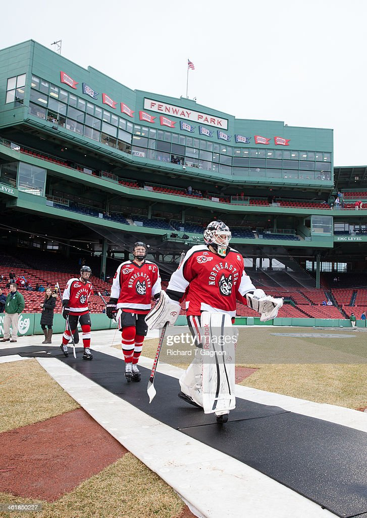 Clay Witt #31 of the Northeastern University Huskies leads his teammates Josh Manson #3 and Adam Reid #8 to the ice before NCAA hockey action against the Massachusetts Lowell River Hawks in the 'Citi Frozen Fenway 2014' at Fenway Park on January 11, 2014 in Boston, Massachusetts.