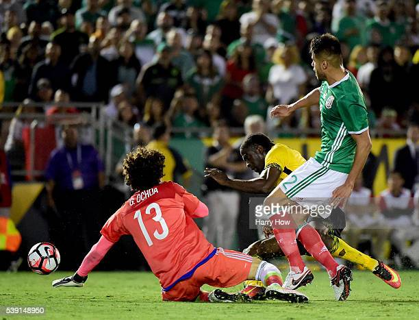 Clayton Donaldson of Jamaica has his shot blocked by Guillermo Ochoa and Nestor Araujo of Mexico during Copa America Centenario at Rose Bowl on June...
