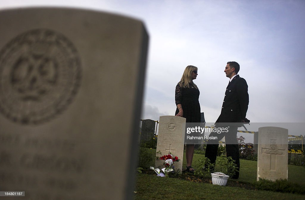 Clayton Ford (R), who led the search and rescue project at the crash site, speaks to a family member of late crew members during the burial of eight RAF crew members at the Commonwealth War Cemetery on October 18, 2012 in Kuala Lumpur, Malaysia. The eight crew members were flying a B-24 Liberator on August 23, 1945, eight days after Japan surrendered in World War II, when the plane crashed and was lost near Kuala Pilah, Malaysia. The crash site was undiscovered until the 1990s and human remains were found in 2009 after a detailed investigation.