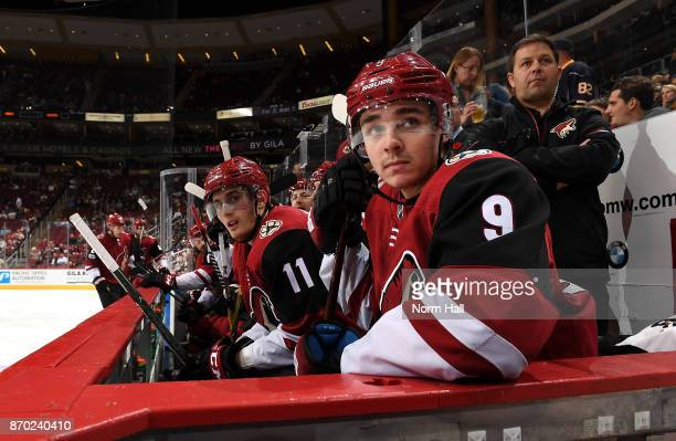 Clayton Keller and Brendan Perlini of the Arizona Coyotes watch the action from the bench against the Buffalo Sabres at Gila River Arena on November...