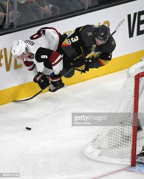 Clayton Keller of the Arizona Coyotes and Brayden McNabb of the Vegas Golden Knights dive after the puck behind the net during the second period of...