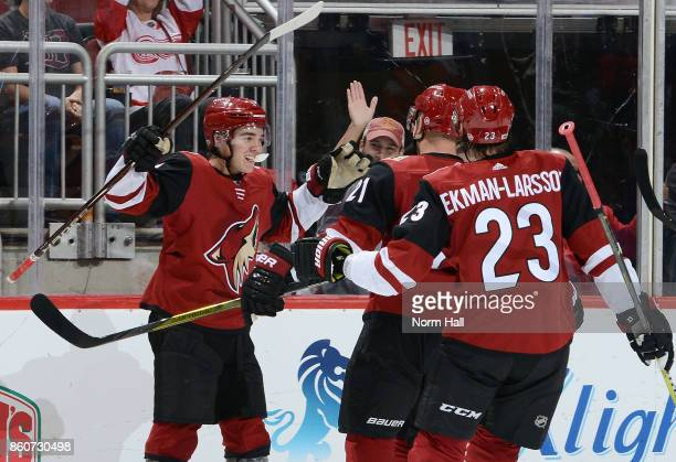 Clayton Keller of the Arizona Coyotes celebrates with teammates Derek Stepan and Oliver EkmanLarsson after scoring a second period goal against the...