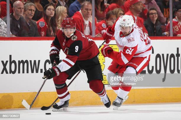 Clayton Keller of the Arizona Coyotes skates with the puck ahead of Xavier Ouellet of the Detroit Red Wings during the second period of the NHL game...