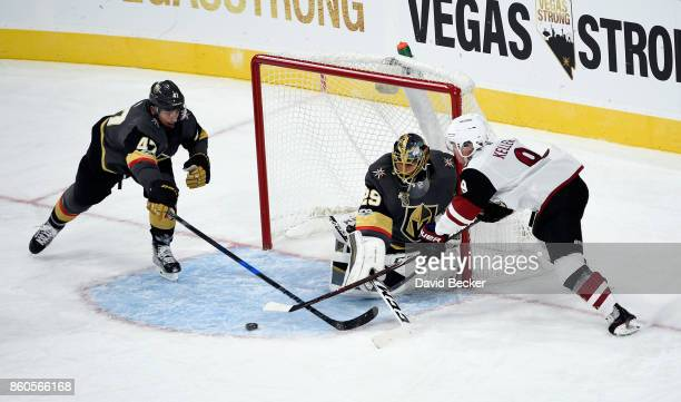 Clayton Keller of the Arizona Coyotes tries to shoot aganst Luca Sbisa and goalie MarcAndre Fleury of the Vegas Golden Knights at TMobile Arena on...